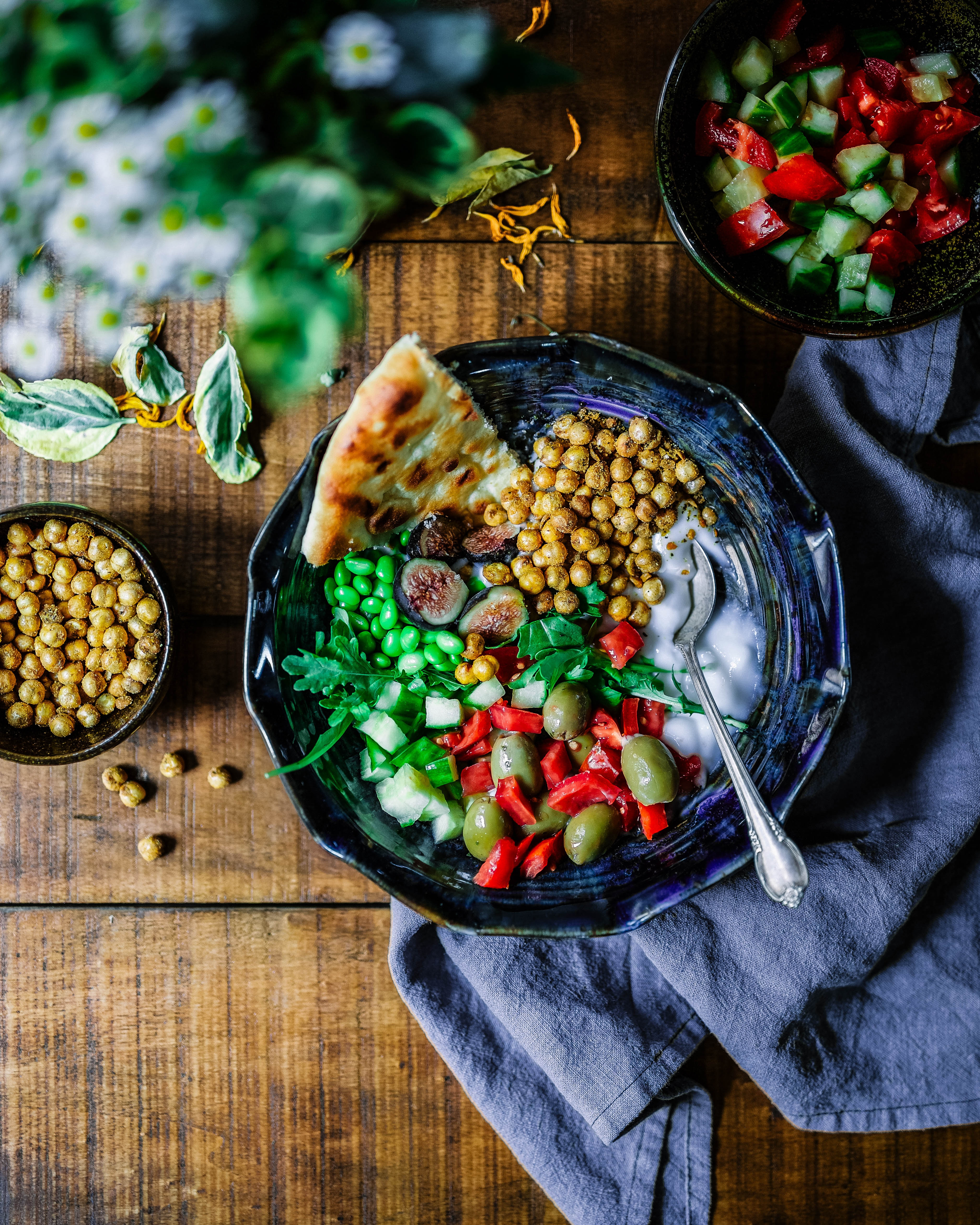 Image shows a blue plate holding yogurt, soy beans, olives, pimentos, chickpeas, flatbread and various other diced vegetables.