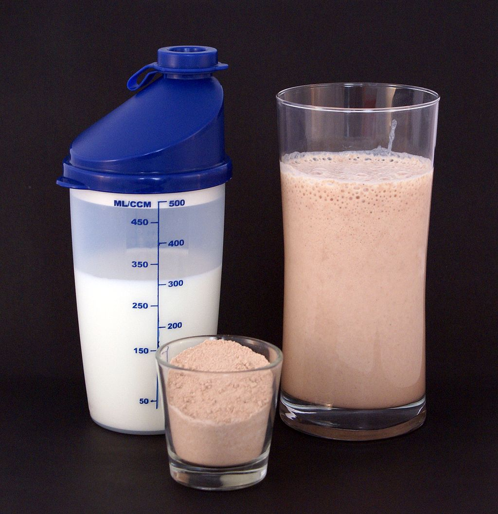 Image shows a glass containing a brown protein shake. Beside the glass are the ingredients used to make the shake: a small container of protein powder and a larger container of milk.