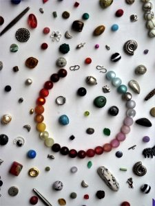 Image shows scattered beads and a beaded bracelet.