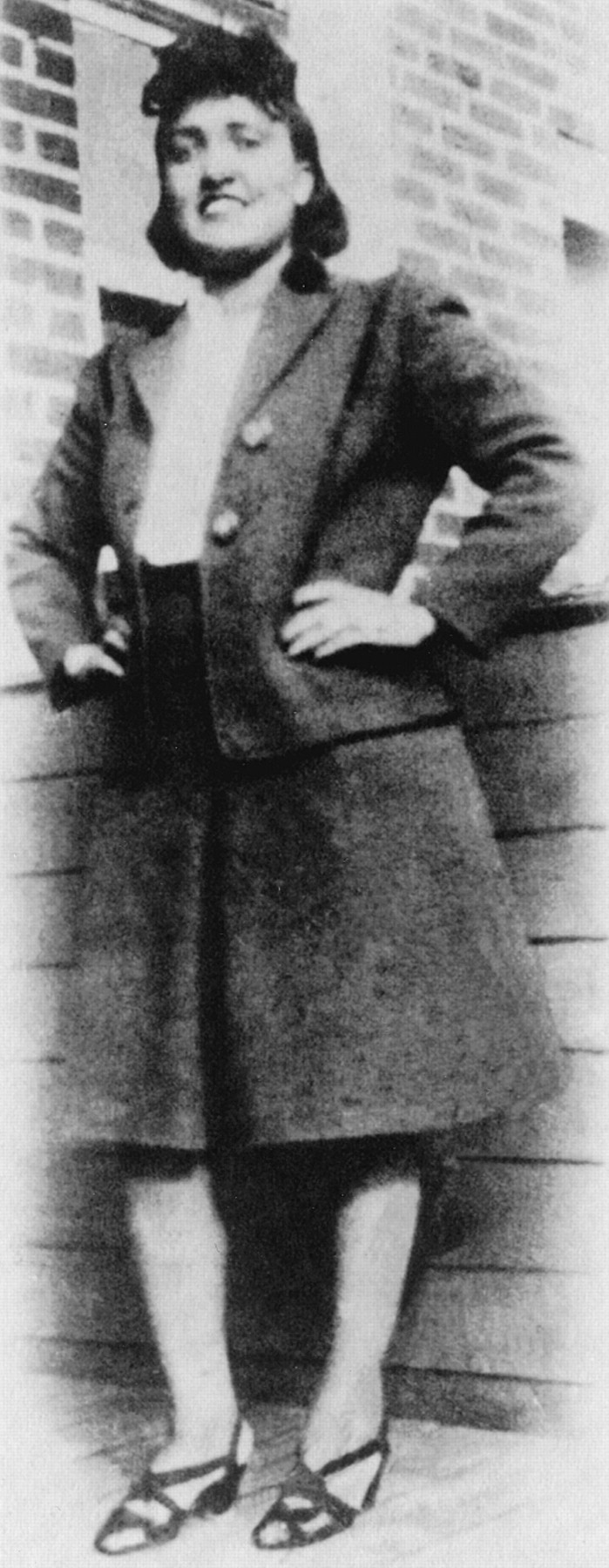Image shows a black and white photograph of a woman smiling, with her hands on her hips. She is African American, and dressed in the style of the 1940s in a skirt and blazer.