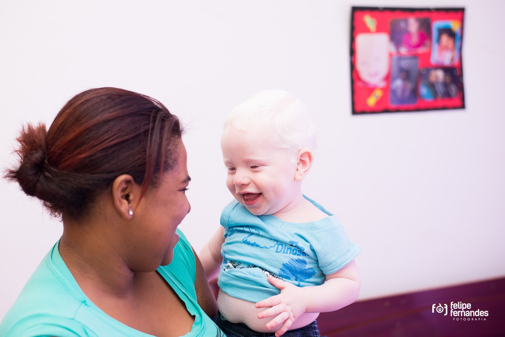 Image shows a young black woman holding and smiling at a delighted 9-month old albino baby.