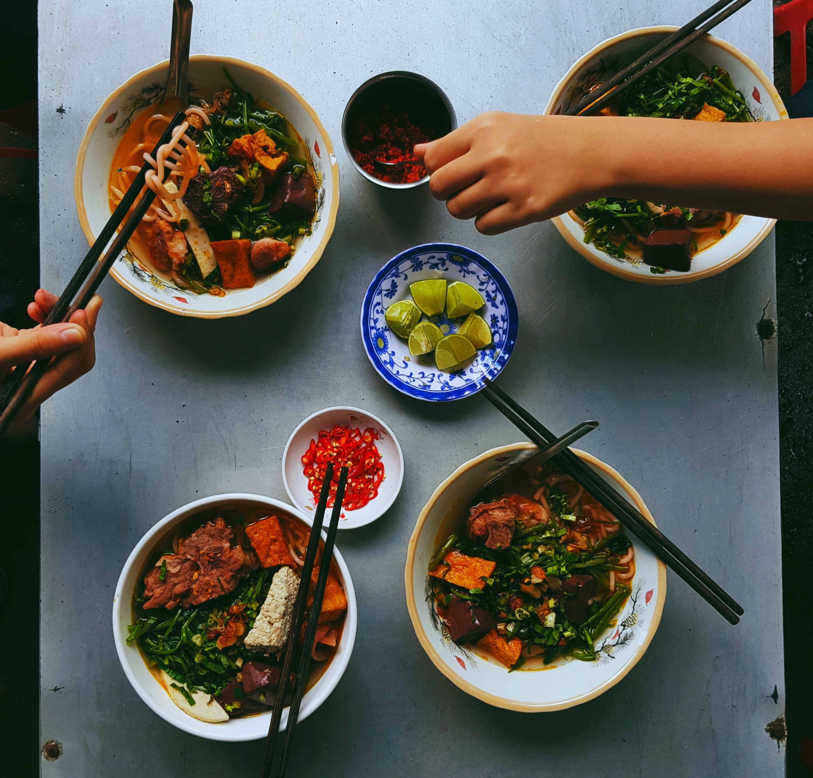 Image shows four bowls of food, each containing noodles, a type of meat, green leafy vegetables and green onions in a broth. Each bowl has chopsticks resting on the side, and there are two smaller bowls in the centre holding lime and chilis.