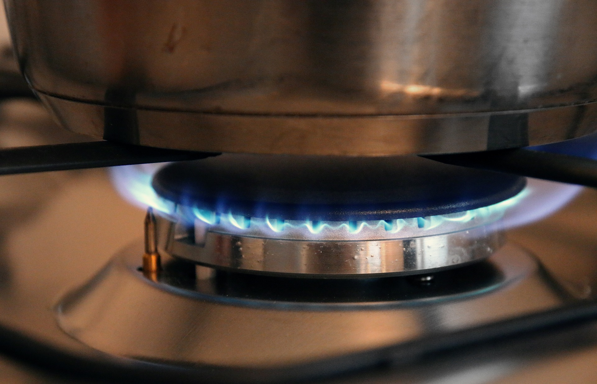 Image shows a lit gas stove burner. The flames are blue and there is a pot on the burner.