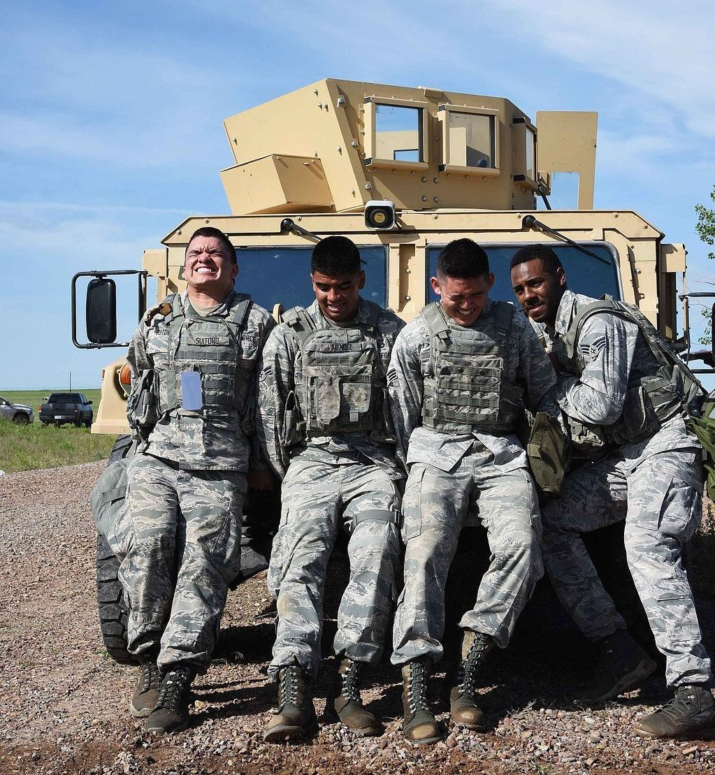 Four soldiers pushing a Humvee. Their backs are against the vehicle and their faces show that they are pushing as hard as they can.