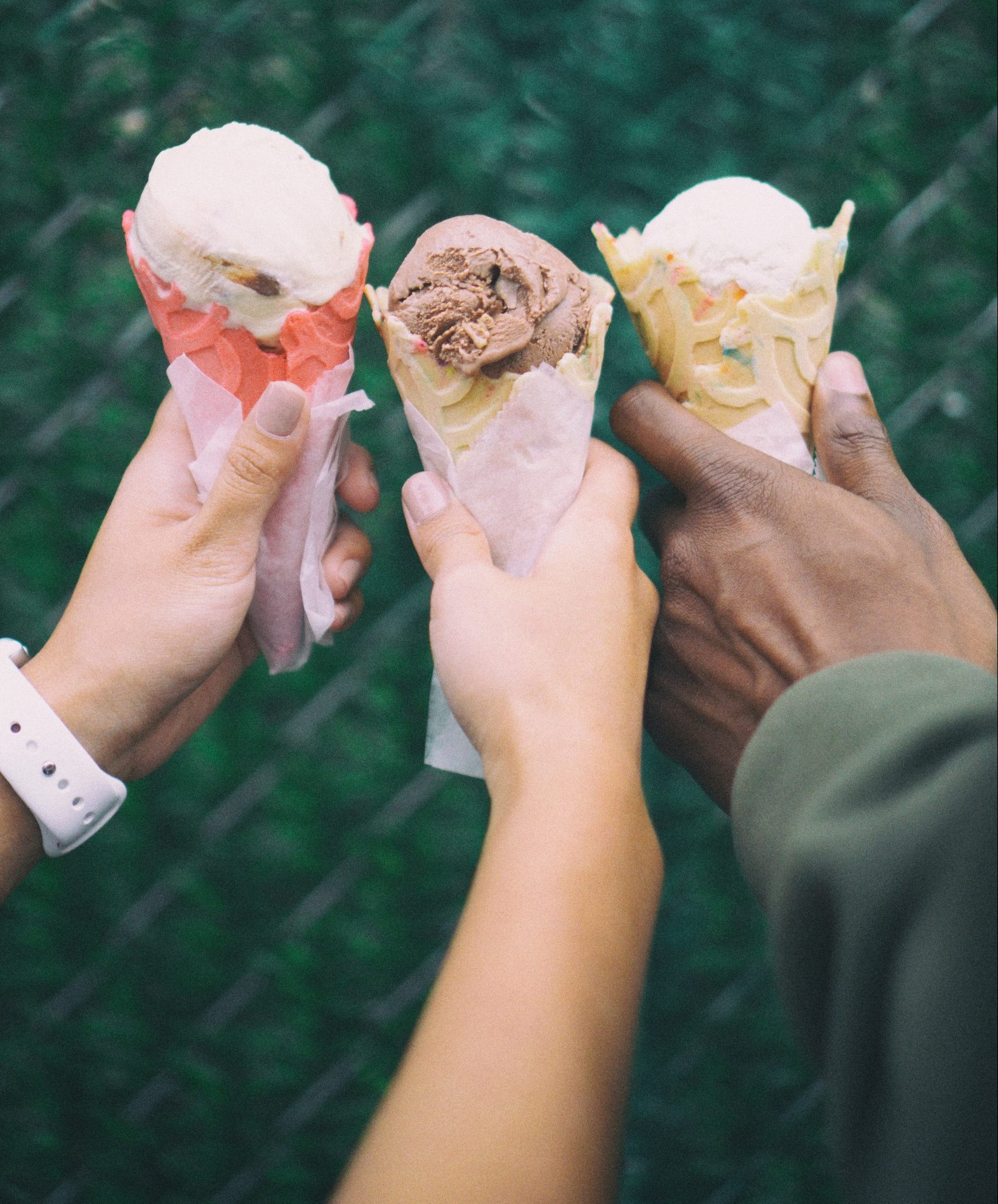The hands of 3 friends, each holding an ice cream cone.