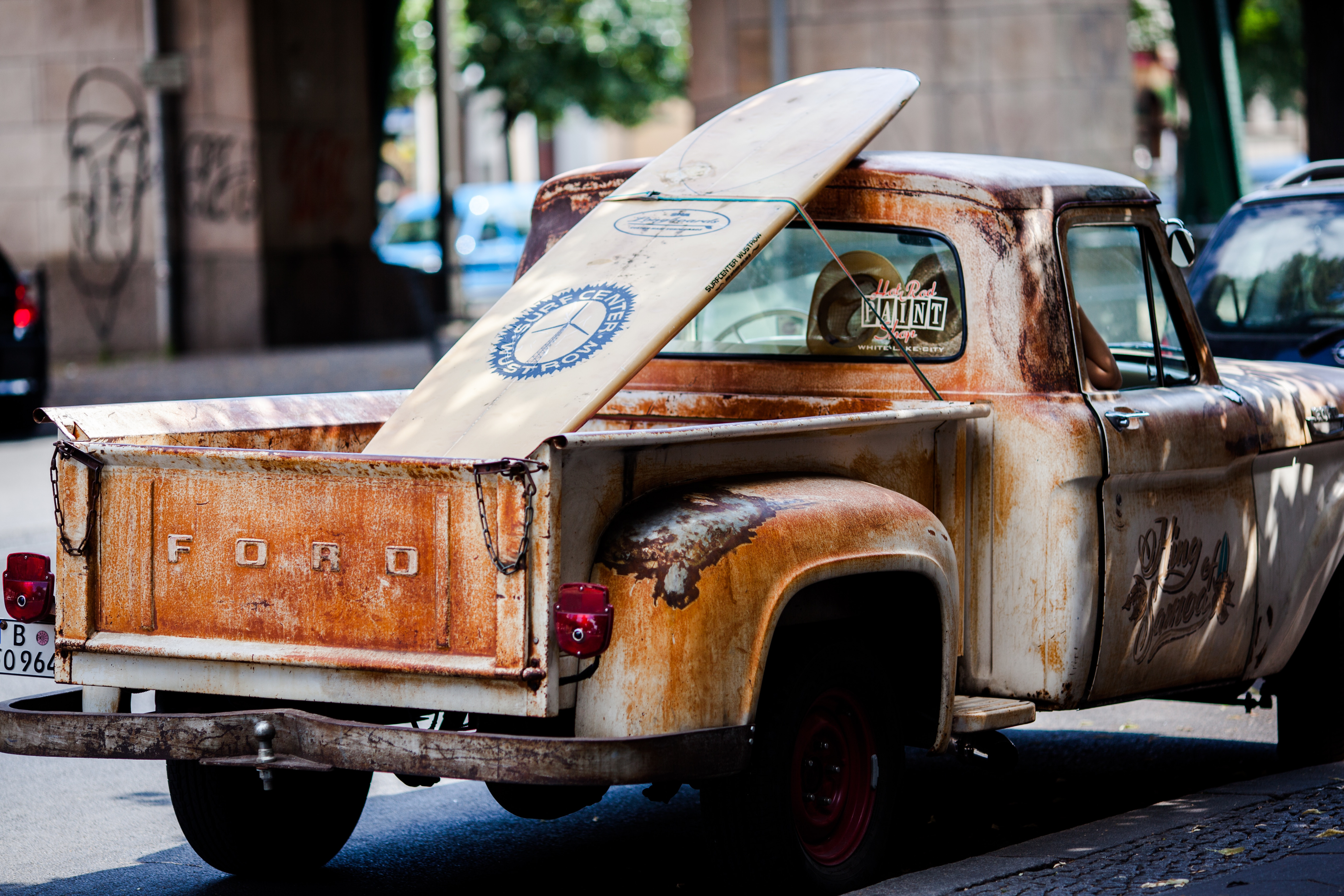 Image shows a very rusty Ford truck with a surfboard in the back.