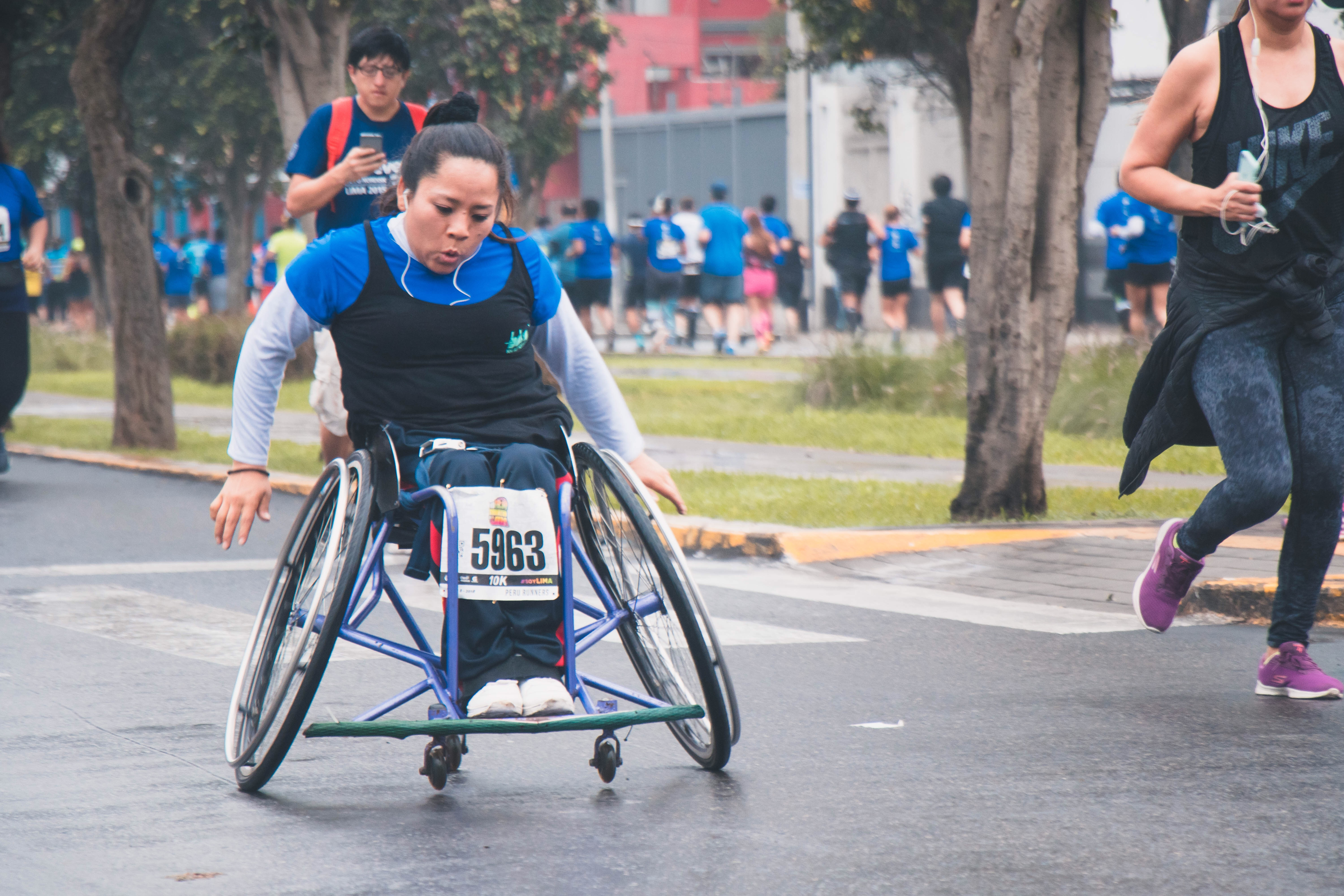 Image shows a woman in a wheelchair taking part in a marathon.
