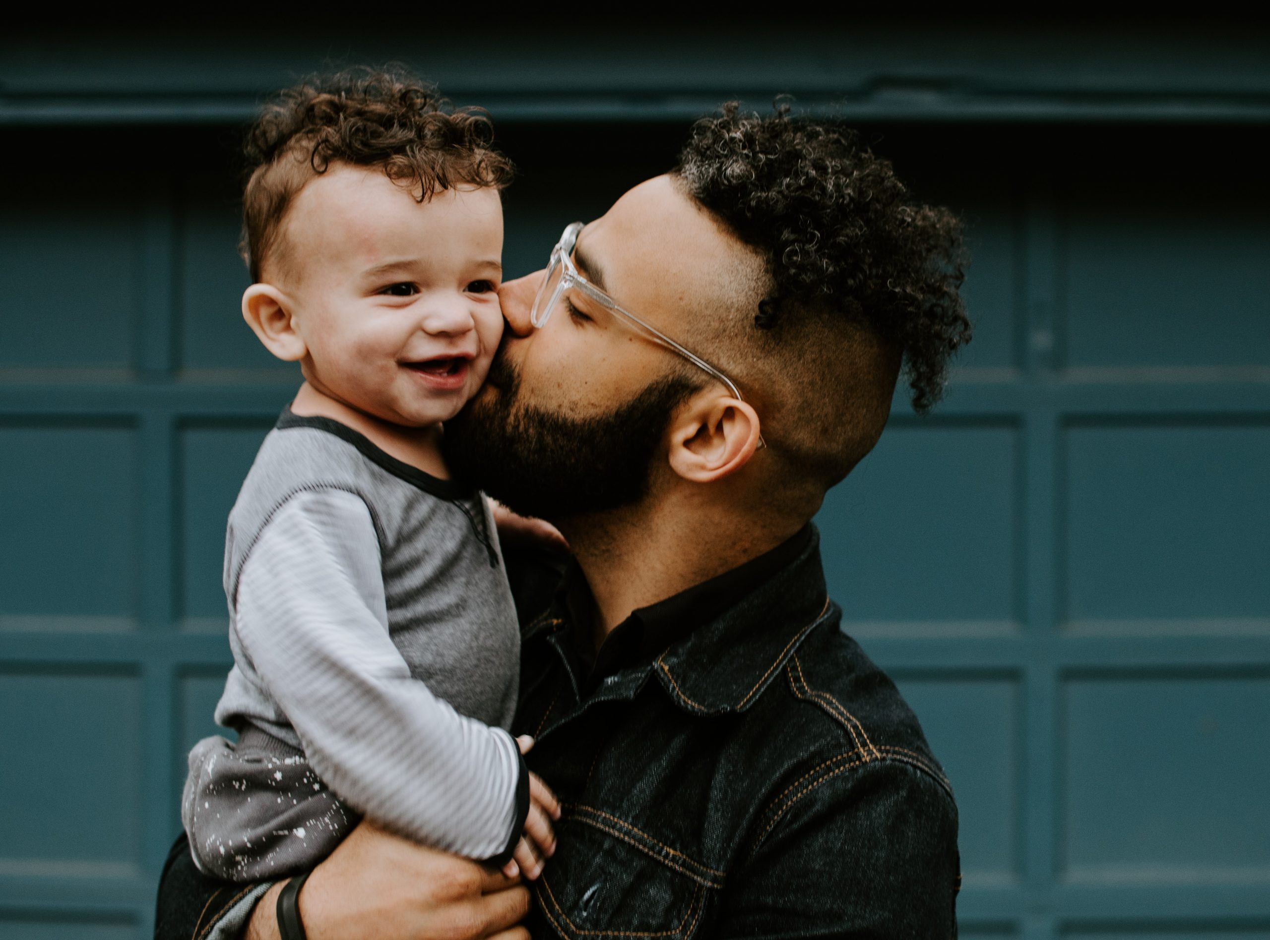 Image shows a dark, curly-haired man in his 20s or 30s holding and kissing a toddler with similar physical features and curly, dark hair, while the toddler smiles.