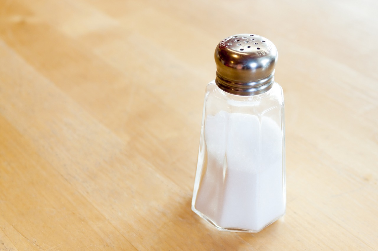 Image shows a salt shaker filled with salt sitting on a wooden counter.